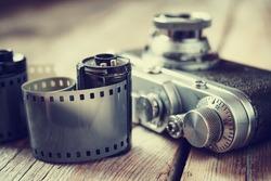 Old photo film roll and retro camera on desk.