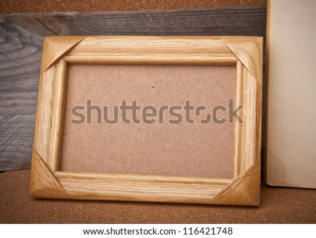 old photo frame and books on the village background - stock photo