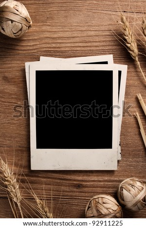 Old photo frames on wood background with wheat