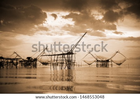 Old photo in sepia warm two tone vintage style, landscapes of Songkhla Lake and fishing square dip net is a local fishing tool rural lifestyle at Pakpra canal, Baan Pak Pra, Phatthalung in Thailand