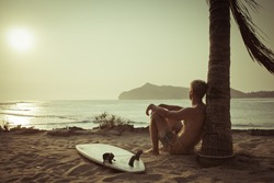 Old photo of surfer near the palm with surfboard on beach