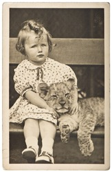 old photo portrait from little girl with tiger baby. vintage picture ca. 1930-40