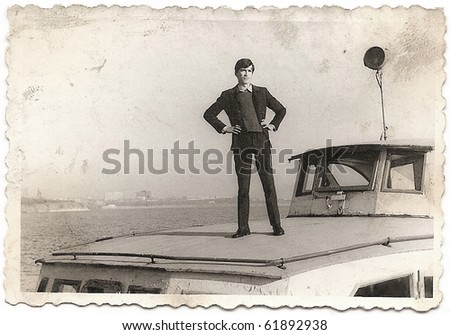 old photograph of a young man posing outdoor on a fishing boat