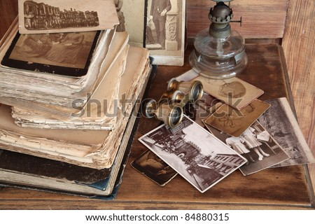Old photos, post cards, books, opera glasses and oil lamp on wooden background.