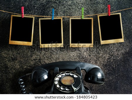 Old picture frame hanging on clothesline and old telephone on grunge background.