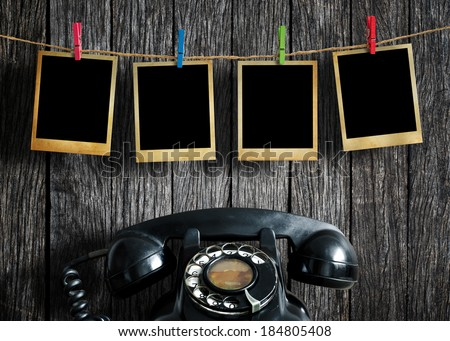 Old picture frame hanging on clothesline and old telephone on wood background.