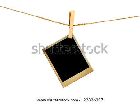Old picture frame hanging on clothesline on white background.