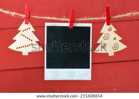 Old pictures on wood background with Christmas decoration.Wooden christmas tree hanging with old picture on rope