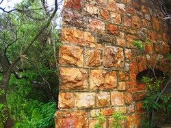 OLD PIECE OF STONE WALL OF A FORT IN RUINS WITH SOME GRAFFITI ON THE SURFACE