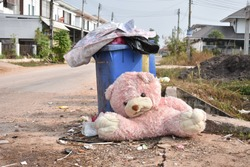 Old pink teddy bears were thrown beside the trash.