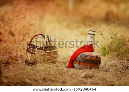 Old pitcher and old basket on yellow background