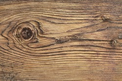 Old plank, with wood knots and cracked, layered rough surface, separated by annual growth lines.