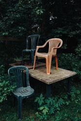 Old plastic chairs stand on a plastic table. Everything was overgrown with greenery. Abstraction of a closed cafe.