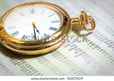 Old pocket watch close up on stock market numbers