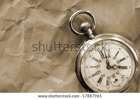 old pocket watch isolated on crinkly paper