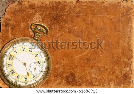 Old pocket watch laying on a worn leather background