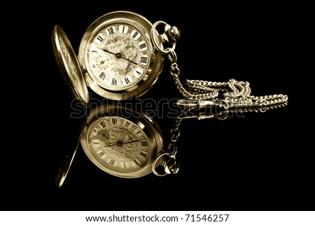 old pocket watch on black background with reflection