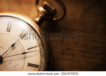 Old pocket watch on grungy wooden desk. Shot in low key and extremely shallow depth for impressional feel. Focus is on etching of clock face plate.