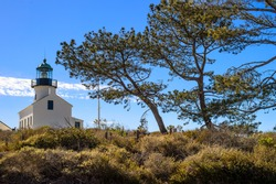 Old Point Loma Lighthouse with blue sky and trees in San Diego, California
