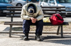 Old poor homeless man or refugee sleeping on the wooden bench on the urban street in the city with bags of clothes on sunny cold day, social documentary concept