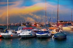 Old port of Constanta with sailing boats and ships on the Black Sea illuminated by sunset