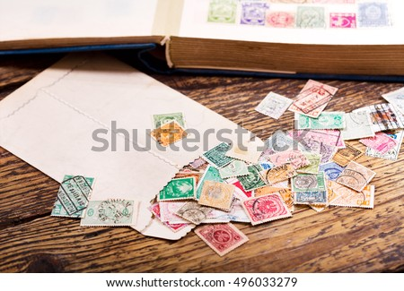 Old postage stamps from various countries on wooden table