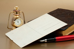 Old postcard, Ink red pen, vintage bronze clock and notepad with reflex