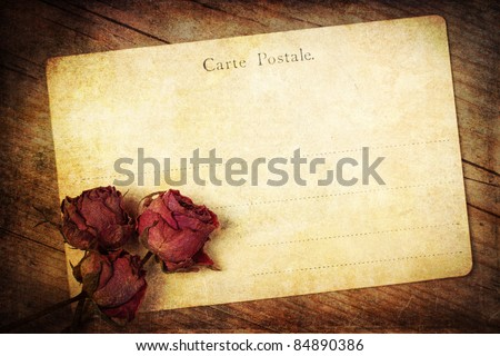 old postcard with dried roses and grunge texture