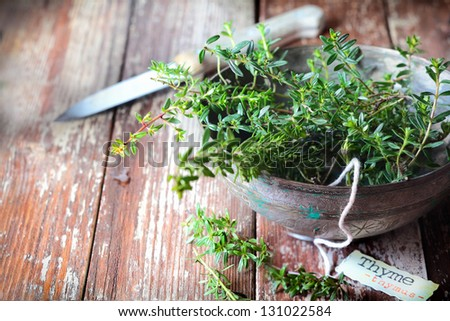 Old pottery bowl full of sprigs of fresh thyme with a decorative name label and kitchen knife on a grunge weathered wooden background