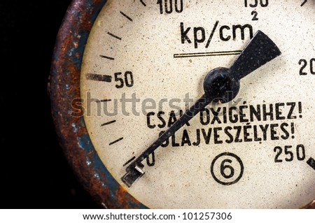 "Old pressure device on black background ""Just for oxygen"" written on it"
