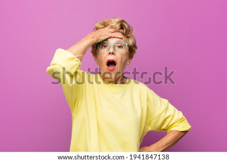 old pretty woman panicking over a forgotten deadline, feeling stressed, having to cover up a mess or mistake Stock photo ©