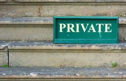 Old Private sign standing on weathered stone steps