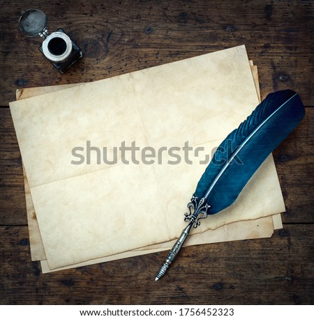 Old quill pen, and old paper blank sheet and vintage inkwell on wooden desk in the old office . Retro style. Conceptual background on history, education, literature topics.