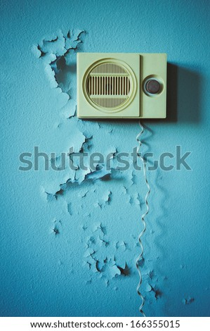 old radio on a wall with old paint