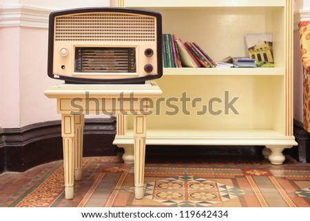 Old radio on stool with book shelf behind them - stock photo