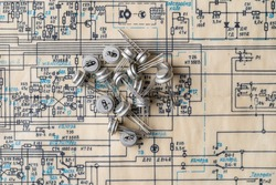 Old radio parts and radio circuit as background for education, electricity industries and repair. Electric radio scheme and transistors from USSR, close up