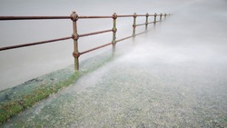 Old railings on a slipway descend into the sea in a long exposure effect