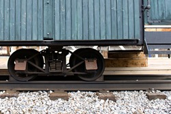 old railroad train wagon on cart with metal wheels