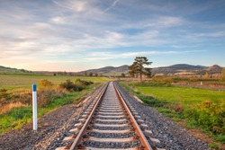 Old Railway tracks running through a field stretching to rural countryside at sunset. Single railway track at sunset, Czech Republic