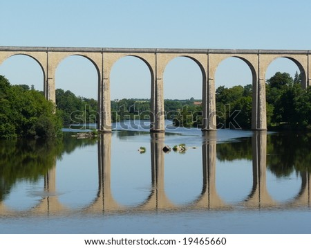 Old railway viaduct and reflection in a river in France