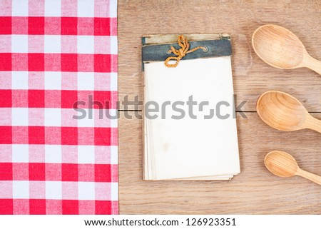 Old recipe notebook, checkered tablecloth, spoons on wooden table background