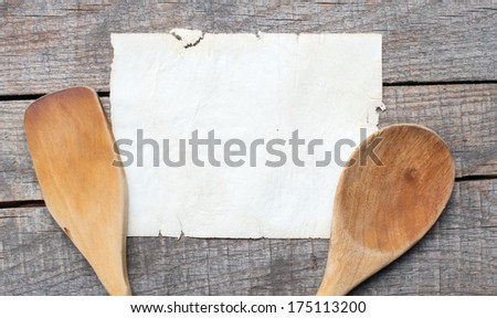 Old recipe notebook, spoons on wood background