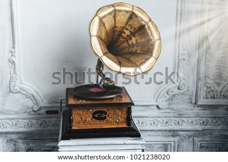 Old record player against ancient wooden wall. Antique gramophone with retro plate produces pleasant sounds or music. Stereo system. Revolution and sound technology concept #1021238020