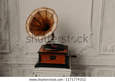 Old record player against ancient wooden wall. Antique gramophone with retro plate produces pleasant sounds or music. Stereo system. Revolution and sound technology concept #1171779352