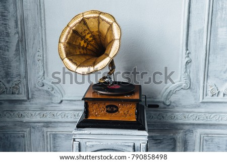 Old record player against ancient wooden wall. Antique gramophone with retro plate produces pleasant sounds or music. Stereo system. Revolution and sound technology concept #790858498