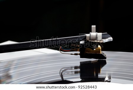 Old record player with focus on the cartridge and stylus on LP