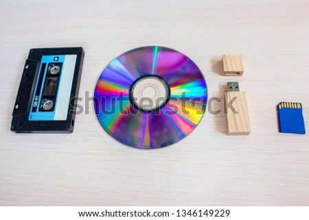 Old recorder cartridge, USB stick, and compact disks in a row.