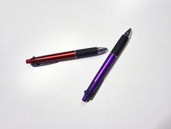 old red ballpoint pen and new purple ballpoint pen