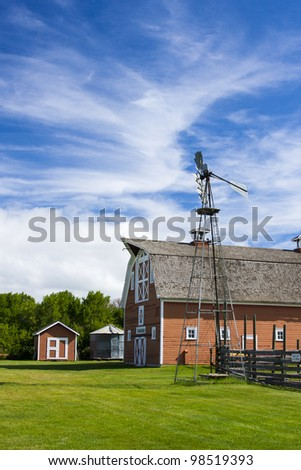 Old red barn and tall metal windmill on a farm