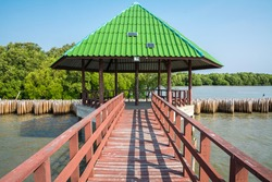 Old red boardwalk bridge for go to the pavilion green roof with a solar cell on the roof and has bamboo wall and mangrove forest in the back of pavilion at Phanthai Norasing, Samut Sakhon, Thailand